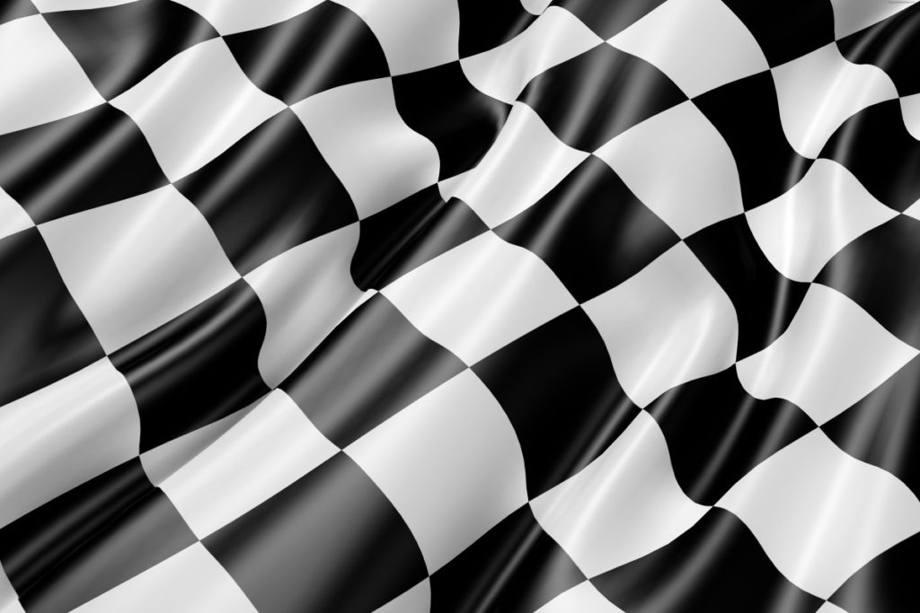 Checkered flags waving at the end of a race.